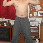 a guy posing sweat pants wrestling mats flexing arms biceps