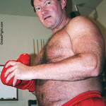 hairy boxer beefy guy putting on gloves